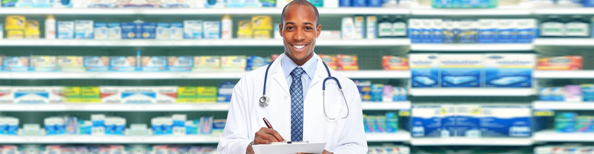 a pharmacist smiling, medicines in the background